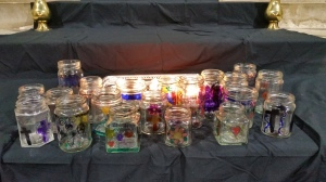 Hand-painted jamjars in front of lighted candles on altar steps of church