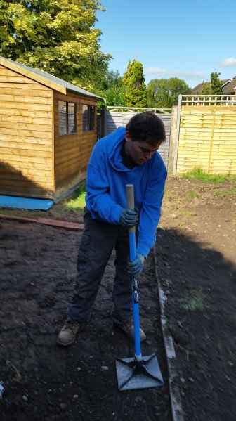 Firming down the soil after sowing seeds to make a wildflower meadow.