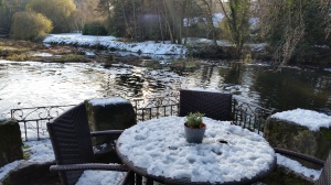 snow laden table overlooking the mill pond and river at the Saxon Mill